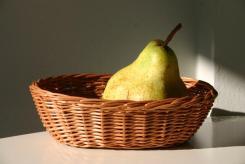 Duża gruszka w małej tacce z wikliny. Wiklinowy Dom